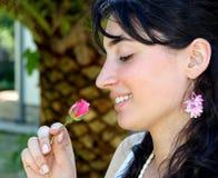το όμορφο κορίτσι αυξήθηκε μυρίζοντας Στοκ Φωτογραφία