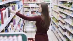 Το όμορφο κορίτσι βάζει τα προϊόντα στο καροτσάκι στο τμήμα καλλυντικών απόθεμα βίντεο