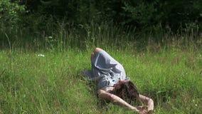 Το όμορφο κορίτσι βρίσκεται στη χλόη, κτυπήματα και εξετάζει τη κάμερα απόθεμα βίντεο