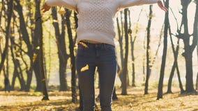 Το όμορφο κορίτσι γιορτάζει το επίτευγμα και πετά τα φύλλα επάνω από το κεφάλι της, επιτυχία φιλμ μικρού μήκους