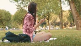 Το όμορφο κορίτσι δακτυλογραφεί το μήνυμα στο smartphone απόθεμα βίντεο