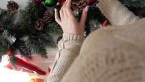 Το όμορφο κορίτσι διακοσμεί το σπίτι με τα παιχνίδια Χριστουγέννων απόθεμα βίντεο