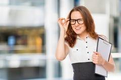 Το όμορφο κορίτσι διορθώνει με το χέρι το πορτρέτο γυαλιών Στοκ Φωτογραφία