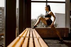 Το όμορφο κορίτσι δυσφήμησης που ντύνεται στη μαύρα αθλητικά κορυφή και τα σορτς κάνει το τέντωμα σε μια ξύλινη στρωματοειδή φλέβ στοκ φωτογραφίες με δικαίωμα ελεύθερης χρήσης