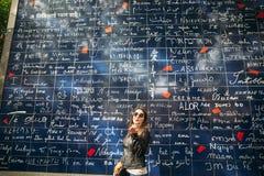 Το όμορφο κορίτσι είναι εισαγώμενο στο Παρίσι κοντά στη βασιλική ο τοίχος της αγάπης στοκ εικόνα
