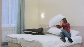 Το όμορφο κορίτσι ενοχλεί το φίλο της, ενώ διάβαζε και η έναρξη ζευγών στην πάλη με τα μαξιλάρια απόθεμα βίντεο