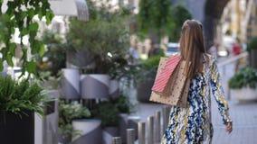 Το όμορφο κορίτσι εξετάζει λατρευτή τοποθέτηση με τις αγορές την οδό Η γυναίκα εξετάζει τη κάμερα και στέλνει ένα φιλί αέρα απόθεμα βίντεο