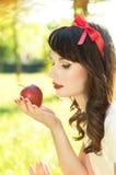 Το όμορφο κορίτσι εξετάζει τη Apple Στοκ Φωτογραφία