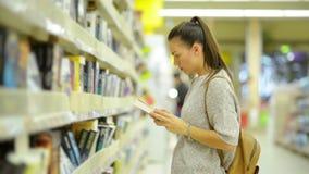 Το όμορφο κορίτσι επιλέγει ένα βιβλίο στην υπεραγορά Η γυναίκα με τη μακριά σκοτεινή τρίχα και το κίτρινο σακίδιο πλάτης παίρνει  απόθεμα βίντεο