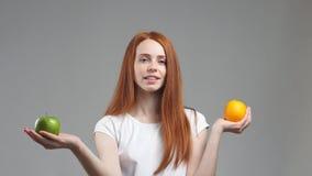 Το όμορφο κορίτσι επιλέγει μεταξύ του πορτοκαλιού ή του μήλου Δόσιμο προτεραιότητας στο πράσινο μήλο απόθεμα βίντεο