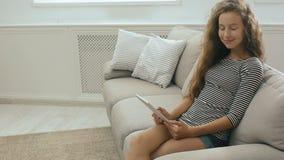 Το όμορφο κορίτσι εφήβων σε έναν καναπέ διαβάζει από μια ταμπλέτα, χαμογελά και κοιτάζει στη κάμερα απόθεμα βίντεο
