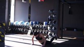 Το όμορφο κορίτσι ικανότητας κάνει την άσκηση ABS στο πάτωμα Να πηδήσουν πίσω και η μπροστινή κλίση σε ετοιμότητα στη σανίδα θέτο απόθεμα βίντεο