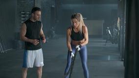 Το όμορφο κορίτσι ικανότητας με τον εκπαιδευτή κάνει την κατάρτιση χρησιμοποιώντας crossfit το σχοινί Workout στη γυμναστική 4k σ