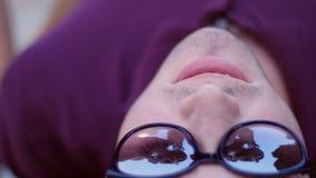 Το όμορφο κορίτσι ισιώνει την τρίχα της - μια αντανάκλαση ενός νεαρού άνδρα με τα γυαλιά που βρίσκεται σε έναν πάγκο στο πάρκο απόθεμα βίντεο