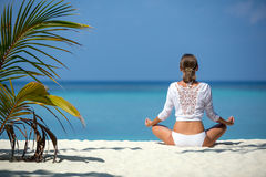 Το όμορφο κορίτσι κάθεται θέτει ενός λωτού και meditates στην ακτή Μαλδίβες Στοκ φωτογραφίες με δικαίωμα ελεύθερης χρήσης