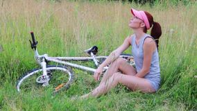 Το όμορφο κορίτσι κάθεται με το ποδήλατο στη χλόη και τα όνειρα στο θερινό βράδυ φιλμ μικρού μήκους