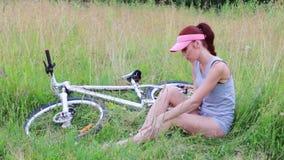 Το όμορφο κορίτσι κάθεται με το ποδήλατο στη χλόη και τρίβει το μωλωπισμένο γόνατό της στο θερινό βράδυ φιλμ μικρού μήκους