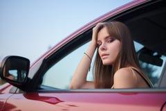 Το όμορφο κορίτσι κάθεται πίσω από τη ρόδα κοιτάζοντας έξω Στοκ Εικόνες