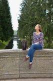 Το όμορφο κορίτσι κάθεται σε μια παλαιά γέφυρα πετρών στοκ εικόνες