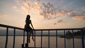 Το όμορφο κορίτσι κάθεται στην αποβάθρα στο ηλιοβασίλεμα και ταλαντεύεται ένα τα πόδια ` s Σκιαγραφία ενός όμορφου κοριτσιού σε έ απόθεμα βίντεο