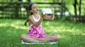 Το όμορφο κορίτσι κάθεται στη χλόη και κάνει selfie στο smartphone του φιλμ μικρού μήκους