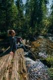 Το όμορφο κορίτσι κάθεται στο κούτσουρο και την κατάψυξη μετά από το ταξίδι Ταξιδιώτης γυναικών στα θερινά περάσματα στην ξύλινη  στοκ εικόνα