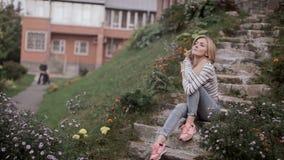 Το όμορφο κορίτσι κάθεται στο μέρος του σπιτιού και κοιτάζει γύρω απόθεμα βίντεο