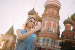 Το όμορφο κορίτσι κάνει μια φωτογραφία στο υπόβαθρο του Κρεμλίνου στοκ φωτογραφίες με δικαίωμα ελεύθερης χρήσης