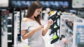 Το όμορφο κορίτσι κάνει τις αγορές στο κατάστημα, βάζει τα αγαθά στο καλάθι, σε αργή κίνηση απόθεμα βίντεο