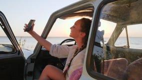 το όμορφο κορίτσι κάνει selfie τη φωτογραφία σε κινητό στο εκλεκτής ποιότητας αυτοκίνητο φιλμ μικρού μήκους