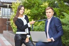 Το όμορφο κορίτσι και ο όμορφος τύπος λειτουργούν στο πάρκο σε έναν υπολογιστή σε ένα φυσικό υπόβαθρο στοκ εικόνες