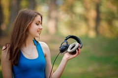 Το όμορφο κορίτσι κοιτάζει στα ακουστικά Στοκ φωτογραφία με δικαίωμα ελεύθερης χρήσης
