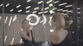 Το όμορφο κορίτσι κοιτάζει στον καθρέφτη φιλμ μικρού μήκους