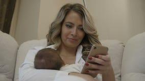 Το όμορφο κορίτσι κοιτάζει στο τηλέφωνο με το μωρό σε ετοιμότητα της απόθεμα βίντεο