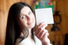 Το όμορφο κορίτσι κρατά ένα καθαρό φύλλο του εγγράφου Στοκ Φωτογραφία