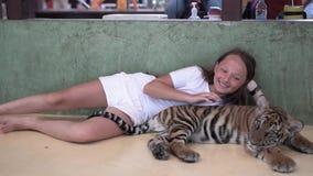 Το όμορφο κορίτσι κτυπά λίγο cub τιγρών και χαμογελά r φιλμ μικρού μήκους