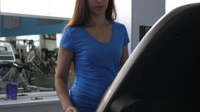 Το όμορφο κορίτσι λεσχών ικανότητας συμμετέχει στο περπατώντας και πόσιμο νερό το κορίτσι treadmill πηγαίνει, καρδιο φορτίο απόθεμα βίντεο