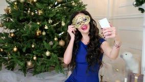 Το όμορφο κορίτσι μεταμφιέσεων Χριστουγέννων στη χρυσή μάσκα κάνει selfie το κινητό τηλεφωνικό selfifoto κατά τη διάρκεια του εορ φιλμ μικρού μήκους