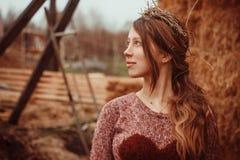 Το όμορφο κορίτσι με ένα στεφάνι του αχύρου στα κεφάλια τους μεταξύ των ξύλινων σανίδων Στοκ Φωτογραφίες