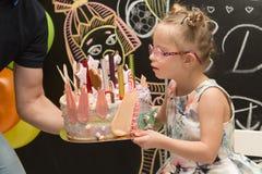 Το όμορφο κορίτσι με το κάτω σύνδρομο που εκρήγνυται σημαδεύει σε ένα κέικ Στοκ Εικόνα