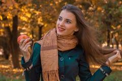 Το όμορφο κορίτσι με μακρυμάλλη και ένα καφετί μαντίλι κρατά τη Apple στο χέρι του φαίνεται μακριά χαμόγελα Στοκ Φωτογραφία