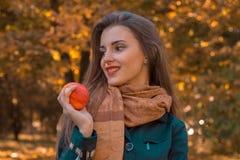 Το όμορφο κορίτσι με μακρυμάλλη και το μαντίλι κοιτάζει μακριά κρατά τη Apple στο χέρι του, κινηματογράφηση σε πρώτο πλάνο Στοκ Εικόνα