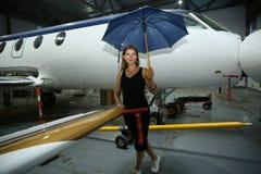 Το όμορφο κορίτσι με μια ομπρέλα περιμένει την πτήση του αεροπλάνου στοκ φωτογραφία με δικαίωμα ελεύθερης χρήσης