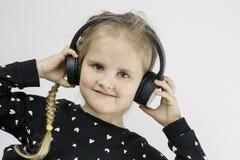 Το όμορφο κορίτσι με τα μεγάλα μαύρα ακουστικά χαμογελά και εξετάζει τη κάμερα στοκ φωτογραφίες