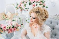Το όμορφο κορίτσι με τα ξανθά μαλλιά σε ένα peignoir κάθεται κομψά στον καναπέ που περιβάλλεται από τα λουλούδια Στοκ φωτογραφίες με δικαίωμα ελεύθερης χρήσης
