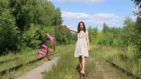 Το όμορφο κορίτσι με την κορδέλλα πηγαίνει στην παλαιά ράγα μεταξύ του δάσους απόθεμα βίντεο