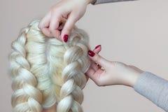 Το όμορφο κορίτσι με την ξανθή τρίχα, κομμωτής υφαίνει μια κινηματογράφηση σε πρώτο πλάνο πλεξουδών, σε ένα σαλόνι ομορφιάς στοκ φωτογραφίες με δικαίωμα ελεύθερης χρήσης