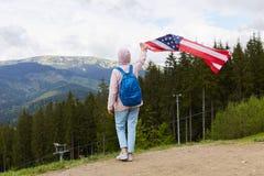 Το όμορφο κορίτσι με τη αμερικανική σημαία που στέκεται προς τα πίσω στη κάμερα στο υπόβαθρο βουνών, υπαίθριος πυροβολισμός της γ στοκ φωτογραφίες