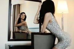 Το όμορφο κορίτσι με τη μακριά σκοτεινή τρίχα φορά το κομψά φόρεμα και τα εξαρτήματα Στοκ Εικόνες