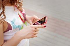 Το όμορφο κορίτσι με τη σγουρή τρίχα που στέκεται στην οδό στο τηλέφωνο υπό εξέταση, στέλνει ένα μήνυμα SMS διαβάζει Στοκ Εικόνα